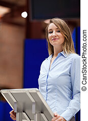Portrait of a woman doing a presentation while looking a the...