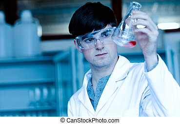 Male scientist looking at an Erlenmeyer flask in a...