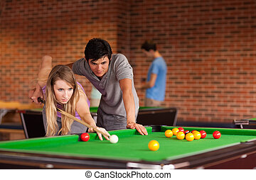 Couple playing snooker in a student home