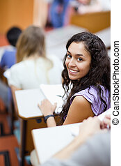 Portrait of a smiling student being distracted in an...