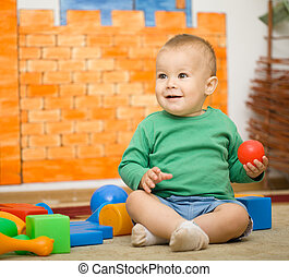 Little boy is playing with toys in preschool while sitting...