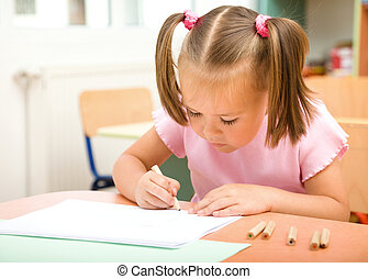 Little girl is drawing with color pencils