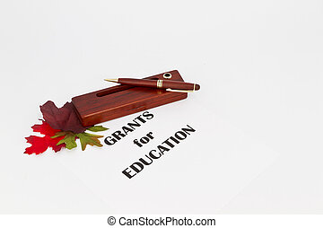 Grants Support Education - Pen and wood pen holder placed on...
