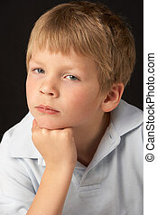 Studio Portrait Of Thoughtful Young Boy