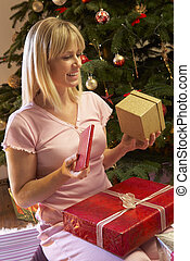 Woman Opening Christmas Present In Front Of Tree
