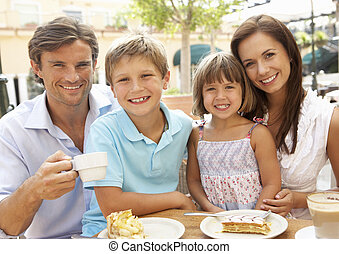 Young Family Enjoying Cup Of Coffee And Cake In Caf? Together
