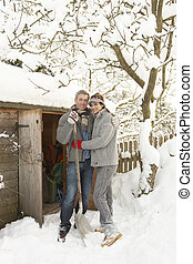 Young Couple Clearing Snow From Path To Wooden Store