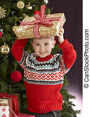 Young Boy Holding Christmas Present In Front Of Christmas Tree
