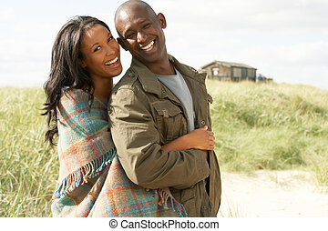 Romantic Young Couple Standing By Dunes With Beach Hut In...
