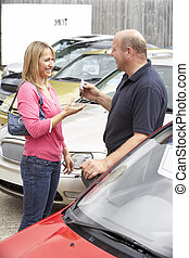 Young woman collecting new car