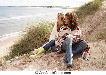 Two Teenage Girls Sitting In Sand Dunes Wrapped In Blanket