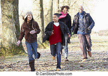 Family Running Through Autumn Countryside