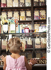 Excited Girl Standing In Sweet Shop