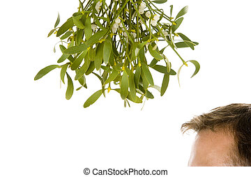 Man waiting under bunch of mistletoe against white...