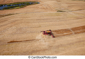 Combine Harvest - A green harvester on the open prairie,...