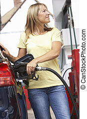 Detail Of Female Motorist Filling Car With Diesel At Petrol Station