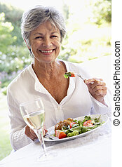 Senior Woman Eating An Al Fresco Lunch