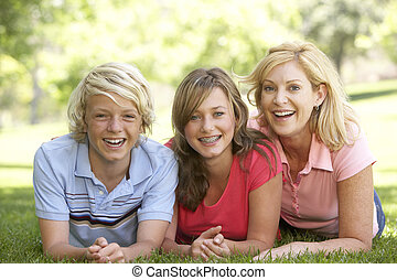 Woman And Her Teenage Children Lying On Grass