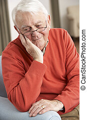 Senior Man Looking Sad In Chair At Home