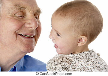 Portrait of grandfather and granddaughter, smiling at each...