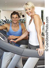 Senior Woman Working With Personal Trainer On Running Machine In Gym