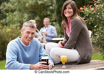 Couple Outdoors Enjoying Drink In Pub Garden