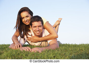 Young couple posing on a field