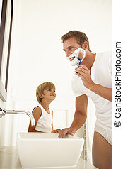 Son Watching Father Shaving In Bathroom Mirror