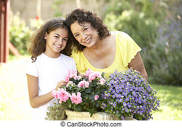 Grandmother And Granddaughter Gardening Together
