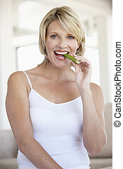 Mid Adult Woman Smiling At Camera And Eating Celery Stick