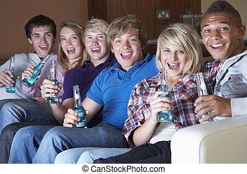 Group Of Teenage Friends Sitting On Sofa At Home Watching...