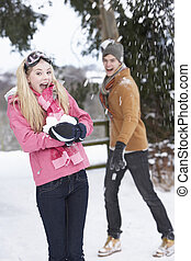 Teenage Couple Having Snowball Fight In Snowy Landscape