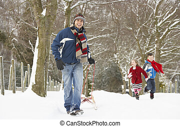Father Pulling Children On Sledge Through Winter Landscape