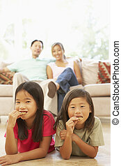 Two Children Eating Cookies At Home