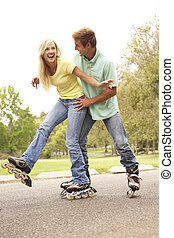 Couple Wearing In Line Skates In Park
