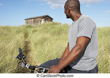 Young Man Riding Mountain Bike By Dunes With Old Beach Hut In Distance