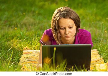 Beautiful woman with a laptop in the park