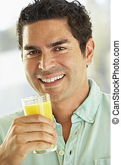 Mid Adult Man Holding A Glass Of Fresh Orange Juice, Smiling At The Camera
