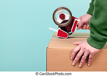 Packaging a box - Photo of a womans hands taping up a...
