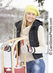 Teenage Girl Holding Sledge In Snowy Landscape