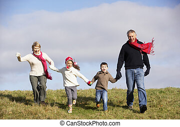 Grandparents And Grandchildren Running In The Park