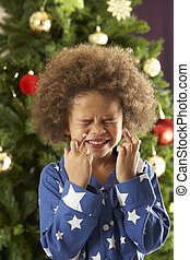 Young Boy Crossing Fingers In Front Of Christmas Tree