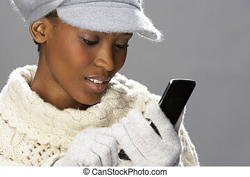 Fashionable Woman Wearing Knitwear And Cap In Studio Using Mobile Phone