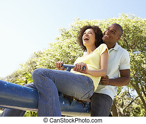 Portrait Of Young Couple Riding On SeeSaw In Park