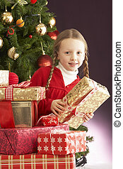 Young Girl Holding Christmas Present In Front Of Christmas...