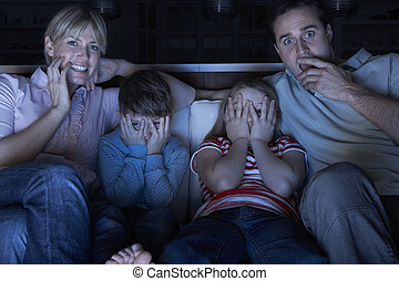 Family Watching Scary Programme On TV Sitting On Sofa...