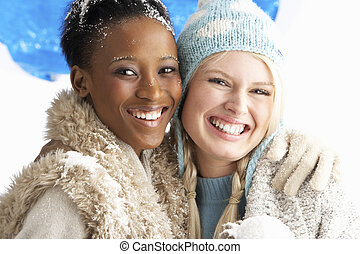 Two Young Women Wearing Warm Winter Clothes Holding Snowball...