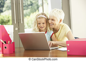 Granddaughter And Grandmother Using Laptop At Home
