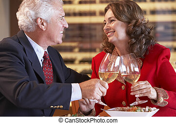 Couple Eating Dinner And Toasting With A Glass Of Wine