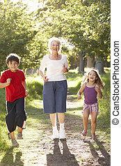 Grandmother Jogging In Park With Grandchildren
